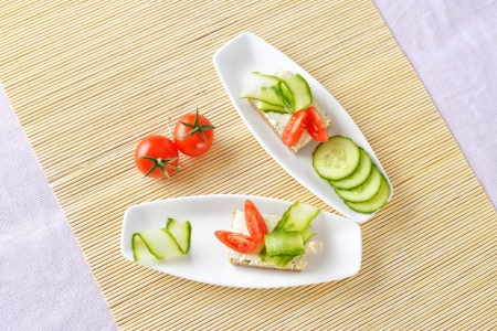 Canapes with butter and vegetables on plate. Top view photo