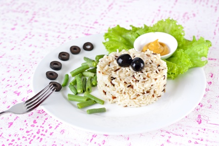 wild rice: Garnish - Bowl of cooked mixed wild Rice. Plate Served with salad and green bean vegetable.