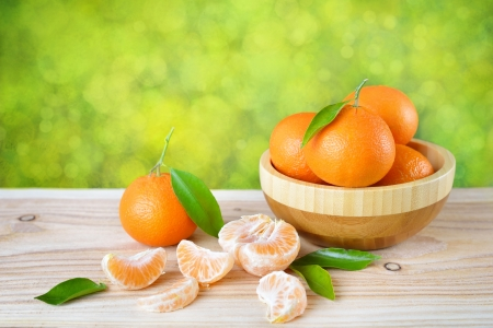 Tangerines with leaves in a wooden plate on a wooden table.