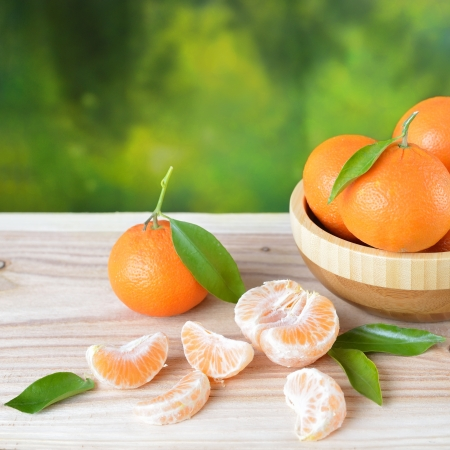 Tangerines with leaves on a wooden table.