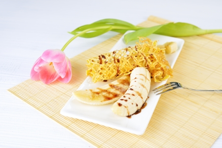 closeup image of a delicious pancakes with banana and chocolate syrup on it. Beautiful tulip flower on the background.