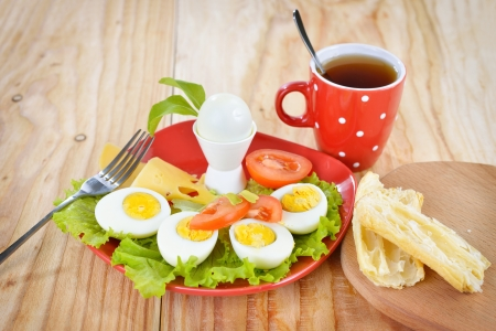 hard boiled: Breakfast with hard boiled eggs, sliced in halves, cup of tea, salad, tomatoes, cheese and bread on the red plate and wooden background