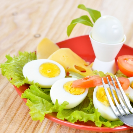hard boiled: Breakfast with hard boiled eggs, sliced in halves, salad, tomatoes and cheese on the red plate and wooden background
