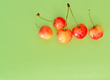 Five Sweet Cherry On Green Background