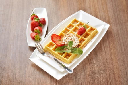 breakfast dessert - golden waffles with ice cream and fresh sliced strawberries sprinkled with sugar and chocolate Stock Photo