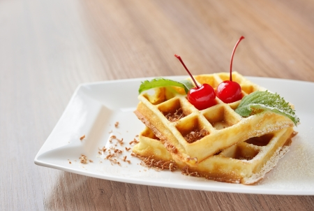 Belgian waffles with cherry sprinkled with sugar and chocolate for dessert or breakfast