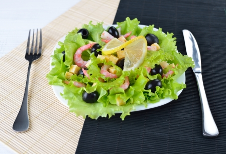 Healthy food background. Vegetable salad with olives, cheese, shrimps and fresh lemon Stock Photo