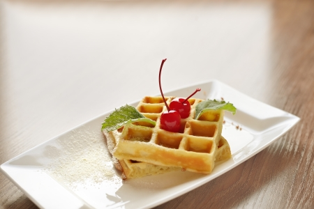 Background of belgian waffles with cherry sprinkled with sugar and chocolate for dessert or breakfask. Space for text