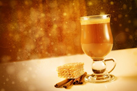 Glass of hot latte coffee with waffles and cinnamon in golden tones