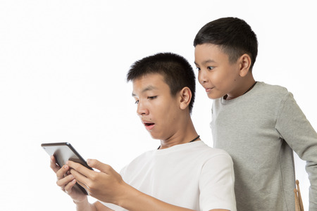 Asian teenager and his brother seeing the surprise on his tablet or ipad photo