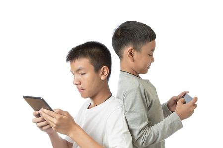 Asian teenager and his brother on tablet and smartphone photo