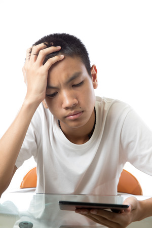 Asian teenager using his tablet on white background and feeling dislike or disappointed Stock Photo