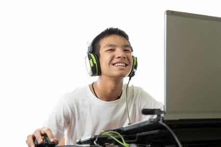 Asian teenager using computer and use a headset to listen to the music at the same time photo