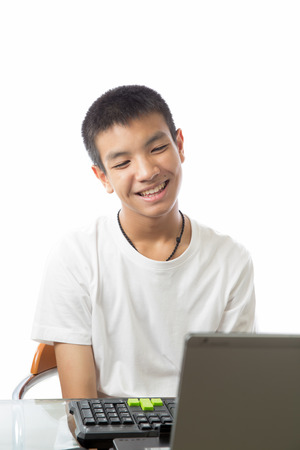 Asian teenager playing computer with smiling on his face photo