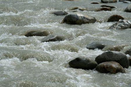 starr: Dunkle und glatte Felsen starr bleiben inmitten turbulenter Str�mung von Wasser