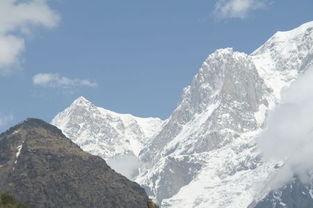Dazzling white snowy Himalayan mountain against bright sky photo