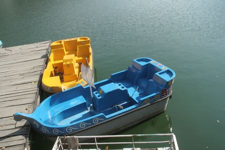 yellow boats: Bright blue and yellow boats at the boarding platform in a lake