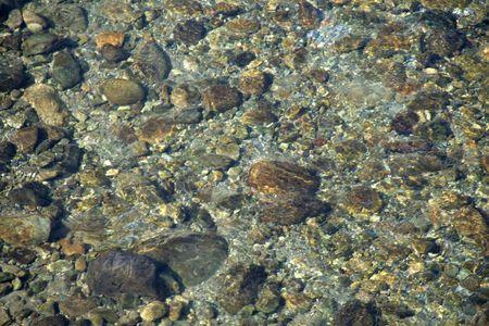 Roches et cailloux � travers la couche transparente de l'eau claire