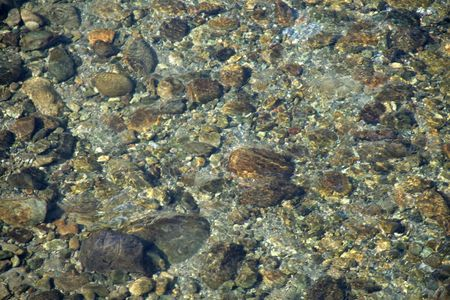 Rocks and pebbles seen through the transparent layer of crystal clear water