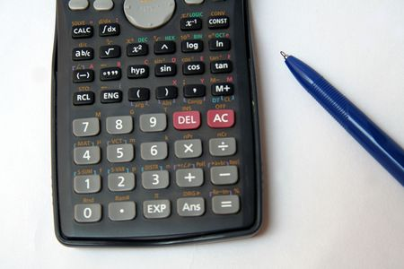 estimating: Calculator and blue ballpoint pen isolated on white Stock Photo