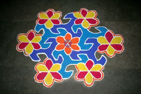 Creation of floral designs in Rangoli art using stone powder mixed with colour