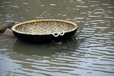 Newly built coracle decked with flowers with row stick