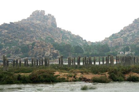 Rocky mountain et pierres piliers du pont vieux abandonn� sur les rives de la rivi�re Tungabhadra, Hampi, Karnataka, en Inde, Asie