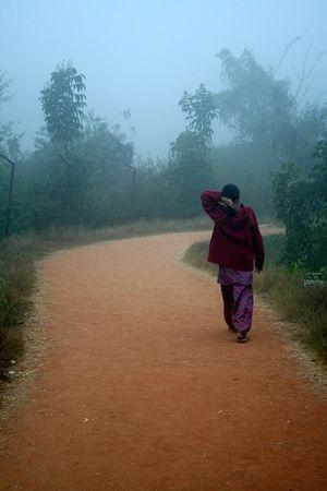 Jeune fille au chandail rouge prenant promenade t�t le matin, brouillard