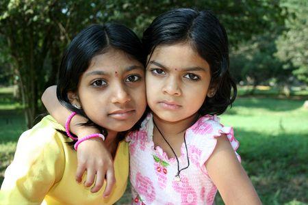 fond of children: Younger sister affectionately putting her arm over the shoulder of her elder sister