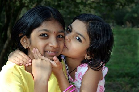 Younger sister affectionately kissing her elder sister
