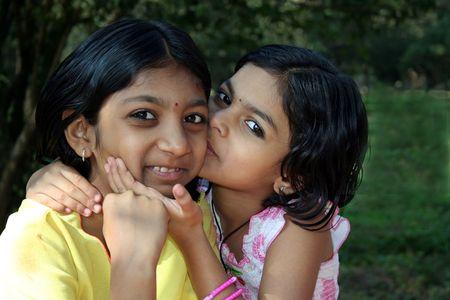 Younger sister affectionately kissing her elder sister