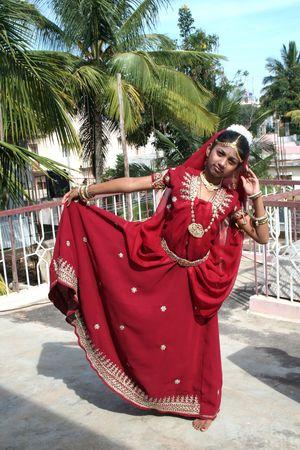 Jeune fille en robe rouge sportives posture de danse Banque d'images