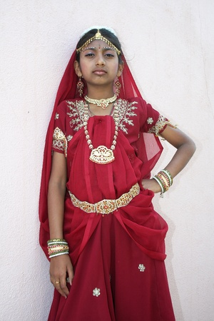 waistband: Girl wearing ornaments on head, neck, waist and hand in red dance costume