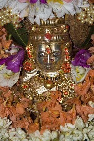 lakshmi: Silver idol of deity Lakshmi copiously decorated with flowers Stock Photo