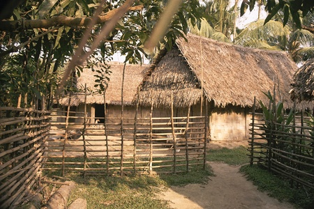 Huts  and the surrounding bamboo fence in a typical In Indian village Stock Photo