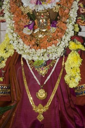 Divinit� porter sari rouge d�cor� avec des ornements d'or et de guirlandes de fleurs est ador� devotionally