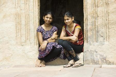 Deux filles dans la disposition heureux assis sur un seuil