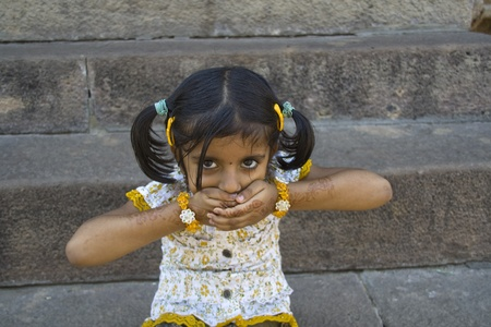 indian child: Tiny tot in 'Shut your mouth' posture with mischievous look Stock Photo