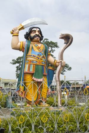Colorful statue of demon Mahishasura holding sword in one hand and serpent in the other hand on Chamundi Hills at Mysore, Karnataka, India, Asia