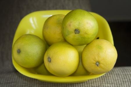 greenish: Yellow and greenish sweet lemons placed in yellow plastic tray