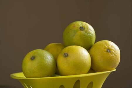 healthful: Limones dulces saludables contra el fondo de color marr�n oscuro Foto de archivo