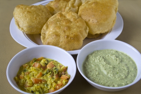 mouth watering: Plate of mouth watering crispy puree with dishes of tasty curry and spicy chutney