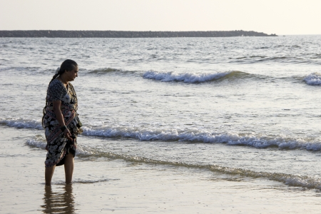 curiously: Woman curiously observing sea waves at Mangalore, Karnataka, India, Asia Stock Photo