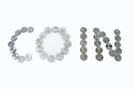 coining: Arrangement of metallic coins to make the word COIN, isolated on white