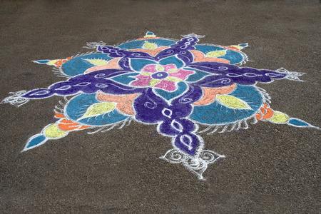 handiwork: Skillful rangoli handiwork design on floor using colored stone powder