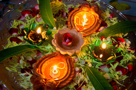 Lighted red earth oil lamps decked with flower petals during festival of Deepavali in India, Asia