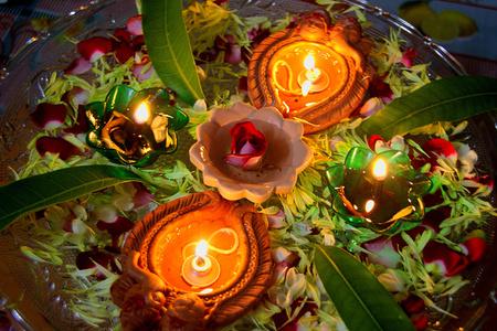 Lampes � huile en terre rouge allum�es orn�es de p�tales de fleurs pendant le festival de Deepavali en Inde, en Asie