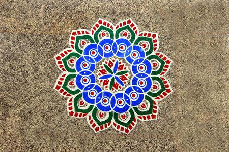 Printed, colorful, geometrical pattern of rangoli stuck on mosaic tiled floor photo