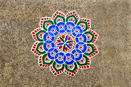 Printed, colorful, geometrical pattern of rangoli stuck on mosaic tiled floor