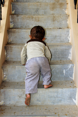 Young baby boy attempting to ascend steps of staircase photo